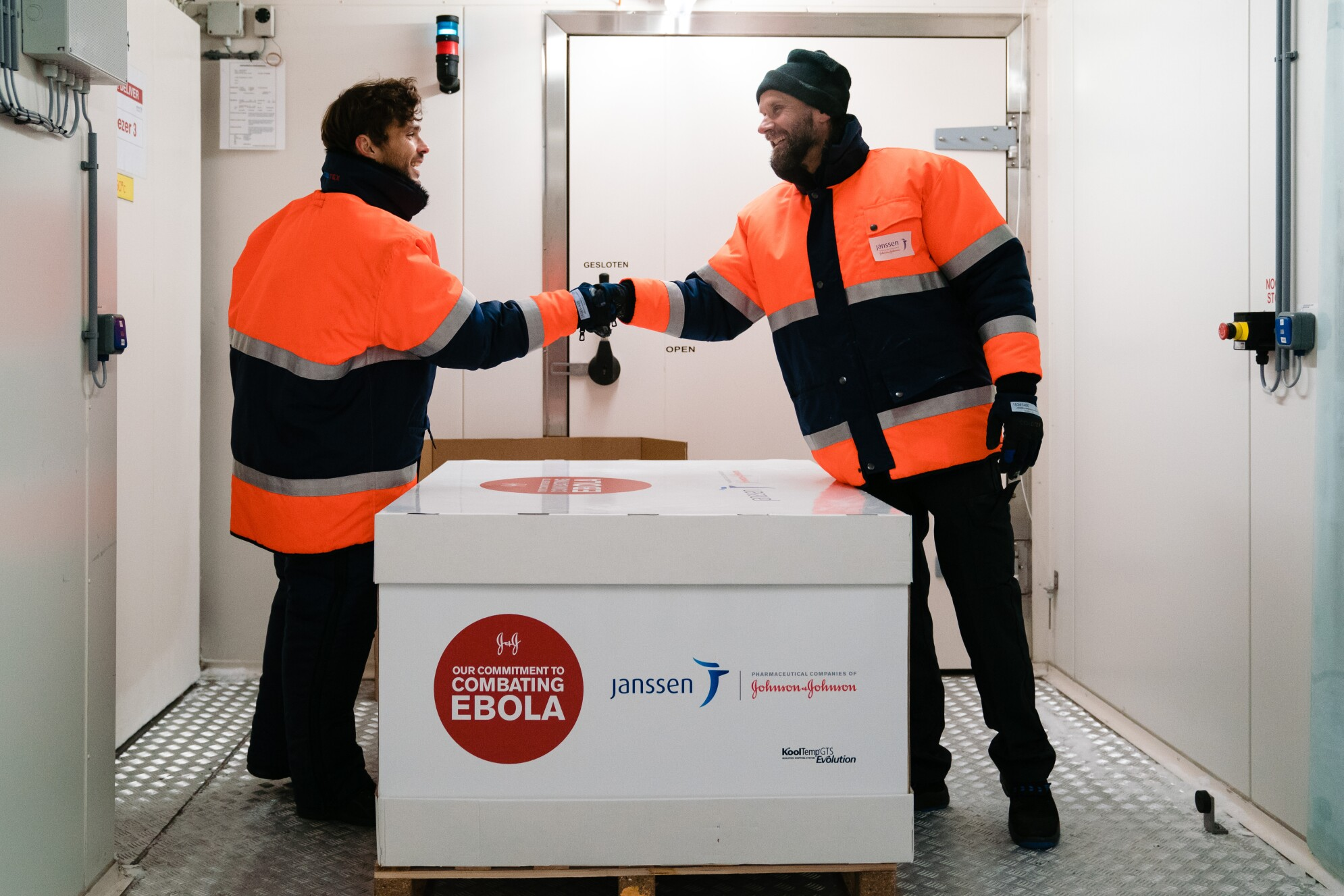 Two men in winter gear shaking hands in front of ebola vaccine shipment