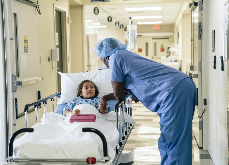 Doctor holding hand of girl in hospital gurney
